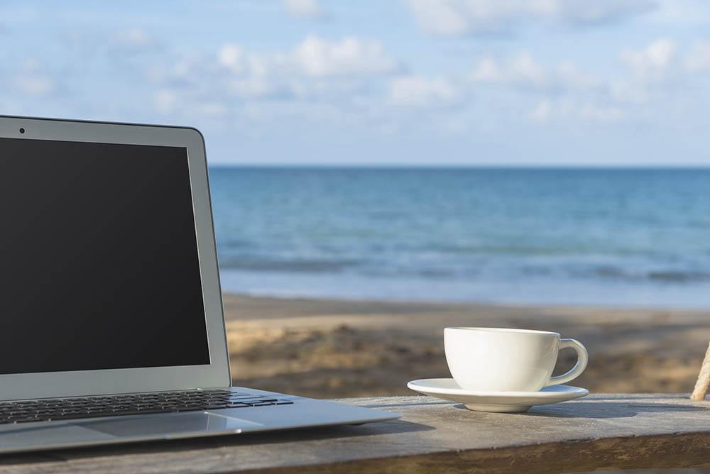 Laptop am Meer – Sinnbild für Zufriedenheit im Job